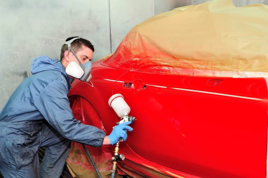 Man painting the side of a red car